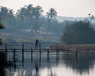 man fishing on bridge at mandrem