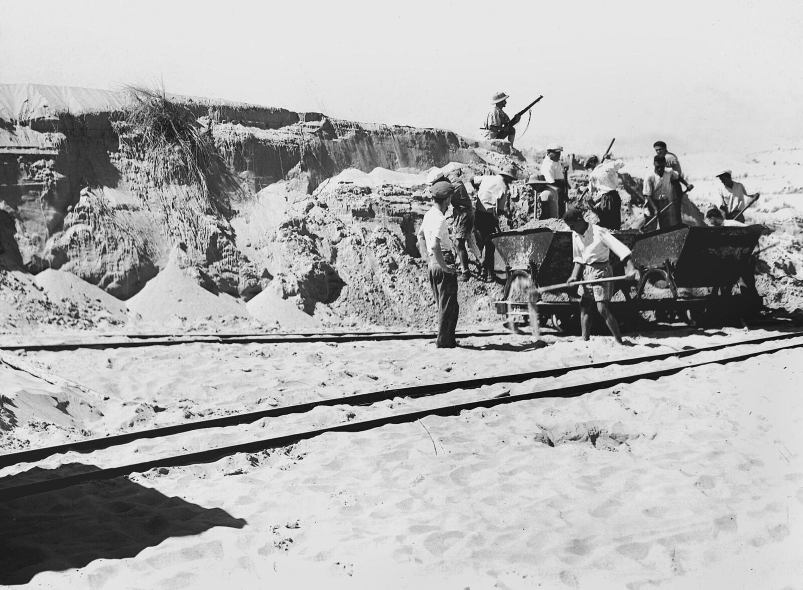 19. 1938. Вооруженная охрана защищает рабочих-евреев, собирающих строительный материал для жилья в новой общине Холон, недалеко от Тель-Авива. 6 октября