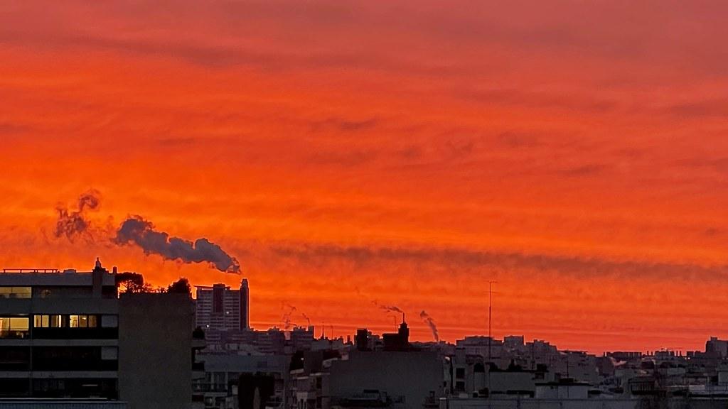 Lever de soleil façon apocalypse : rouge avec un panache de fumée sur la ville