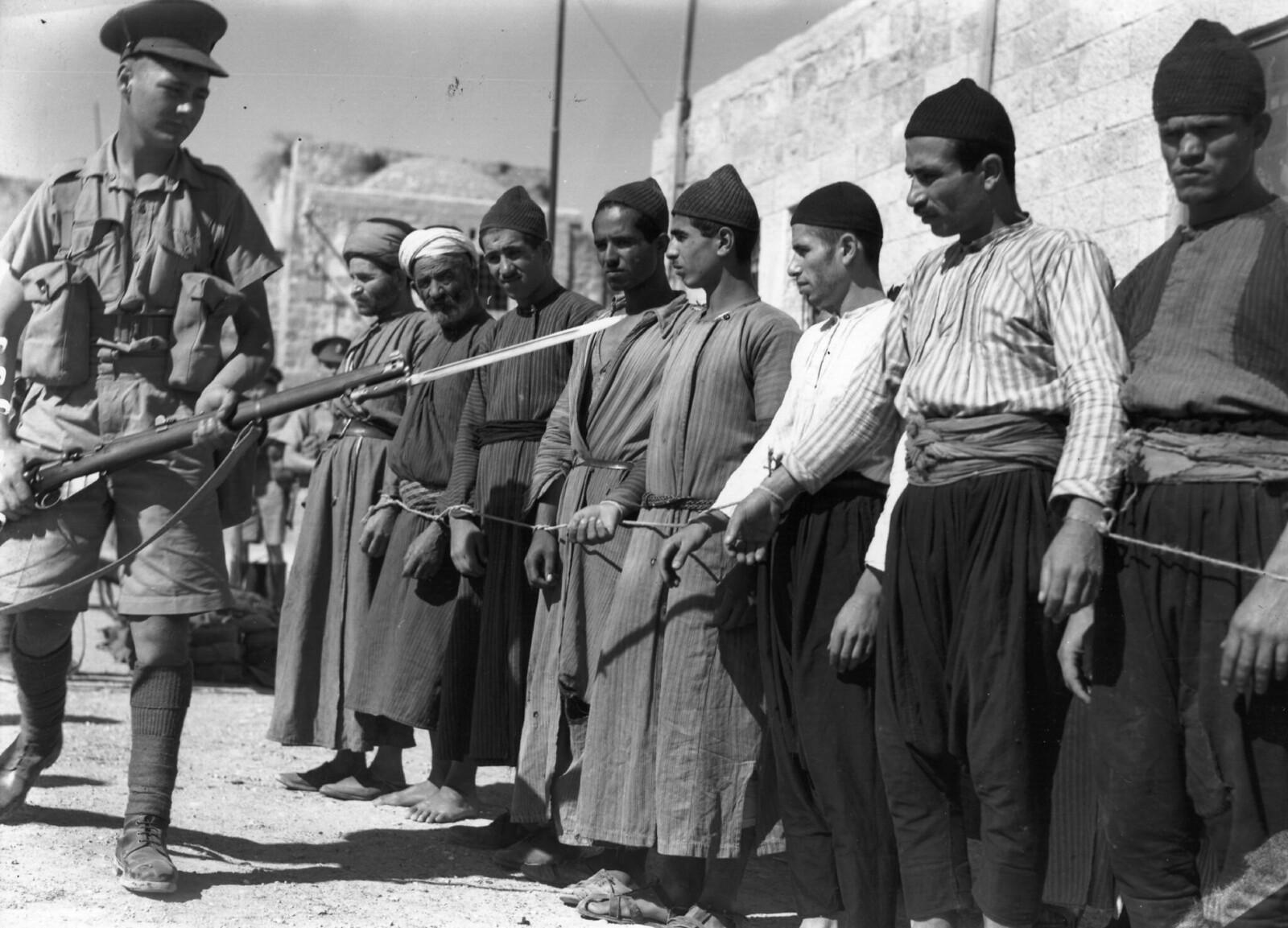 11. 1938. Группу арабских заключенных в Старом городе Иерусалима охраняет солдат, вооруженный винтовкой и штыком. 26 октября