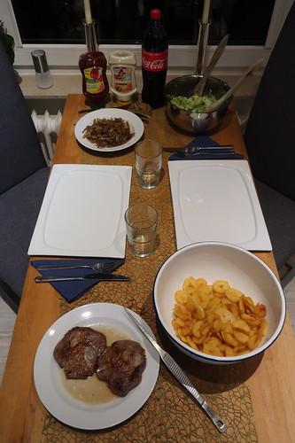 Frittierte Kartoffelscheiben zu Romanasalat und Nackensteaks mit geschmorten Zwiebeln