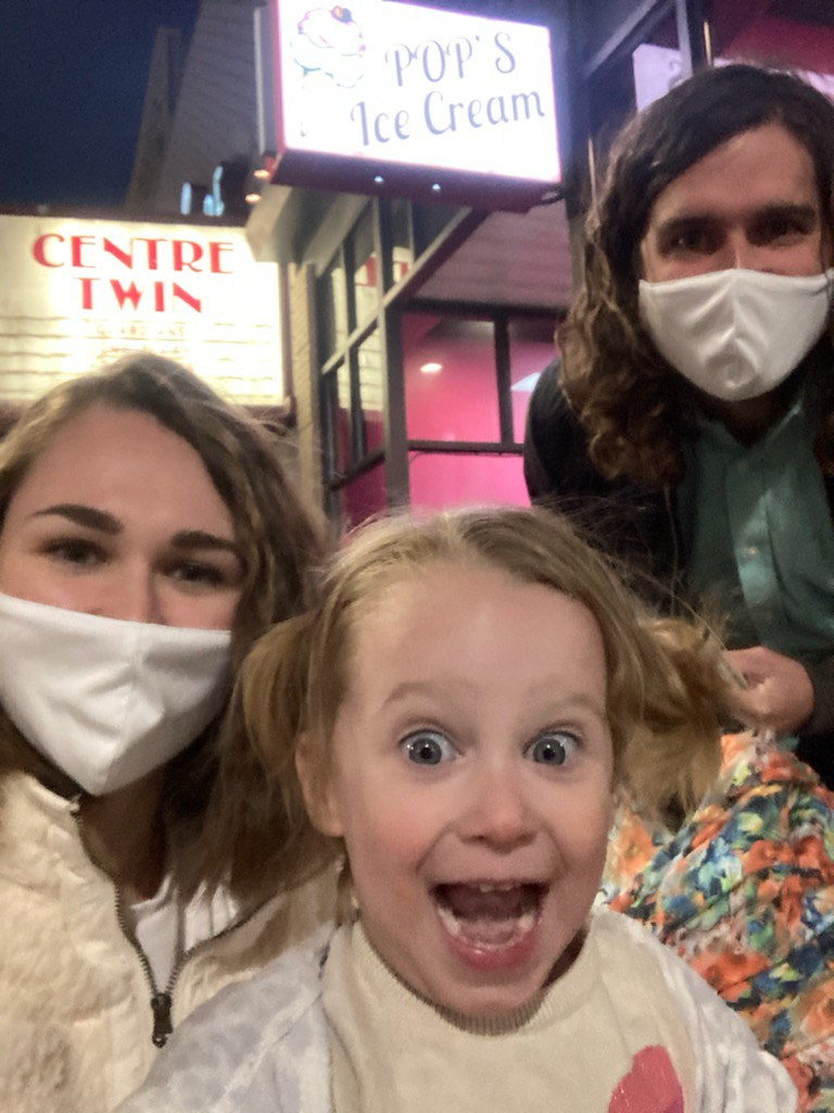 A man and woman wearing masks behind an unmasked two-year-old girl who is smiling with her eyes opened widely. The man is holding an infant's detachable carseat, covered with a blanket. Behind them, a movie theater marquee shines with the words Centre Twin