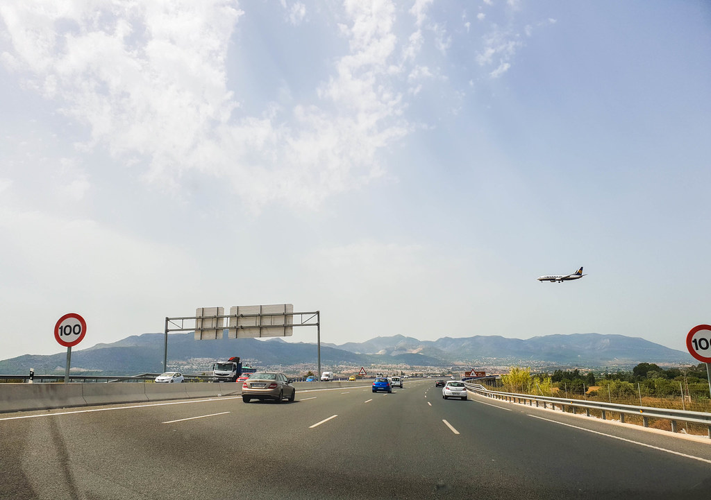 The A7 highway in Spain, with a Ryanair plane landing at Malaga airport approaching the runway passing just above it.