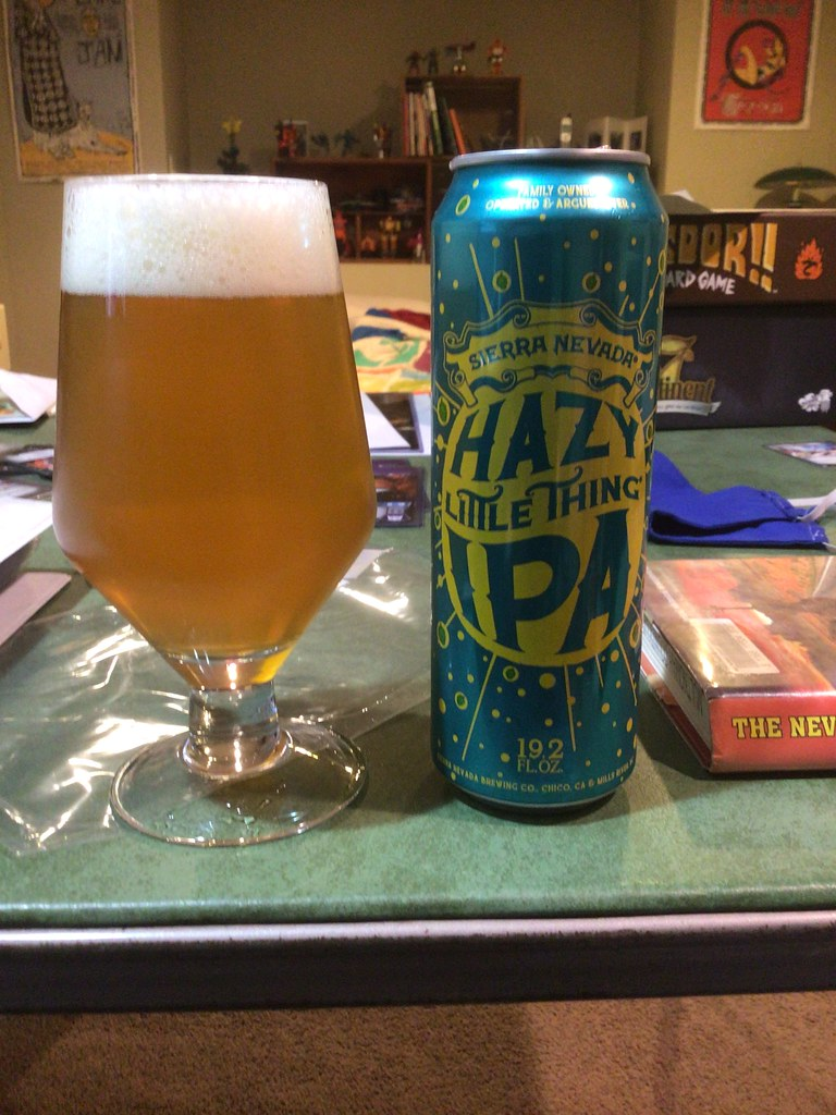 Sierra Nevada Hazy Little Thing IPA in glass, with can, on table indoors
