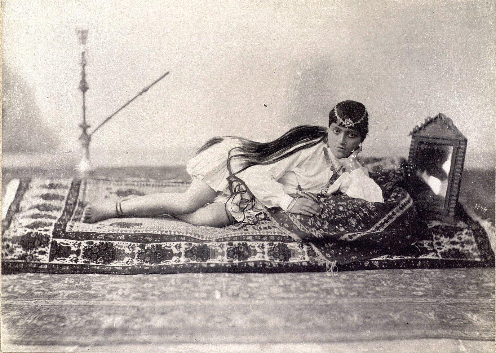 Молодая женщина лежащая на ковре