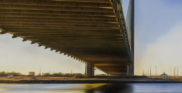 Underside of Indian River Inlet Bridge Illuminated By Reflected Early Morning Sun
