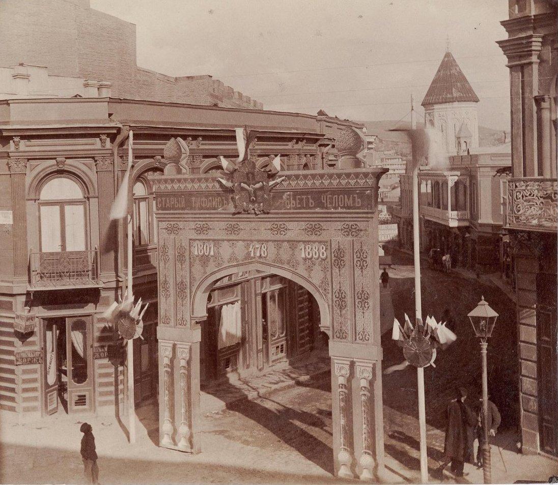 Вид арки на Армянском базаре, в день проезда в Сионский собор императора Александра III. На арке надпись «Старый Тифлисъ бьетъ челом 1801-478-1888». Мушегянц М. 1888