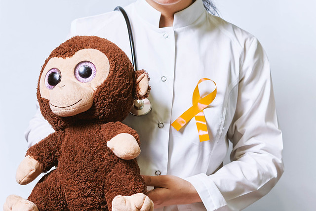Female doctor with pinned Childhood cancer day yellow ribbon holding a kid's plush toy