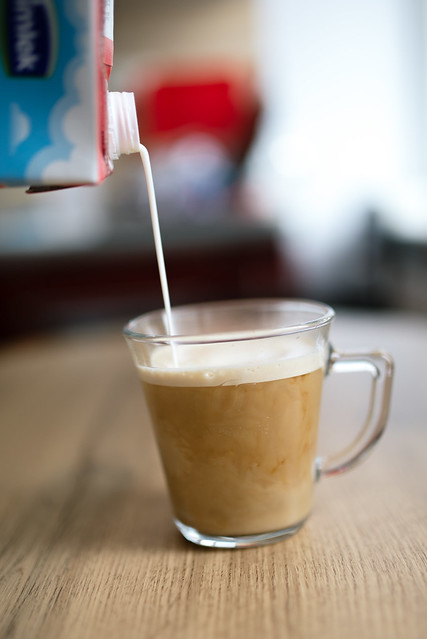 Pouring milk for latte at home closeup.