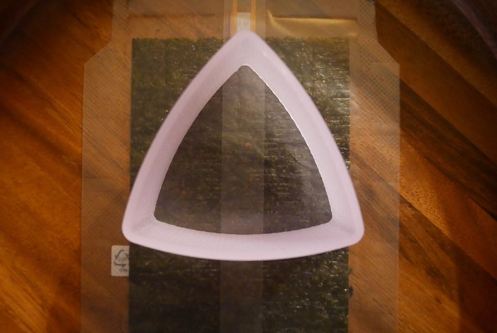 Triangle kimbap mold on top of the seaweed strip.