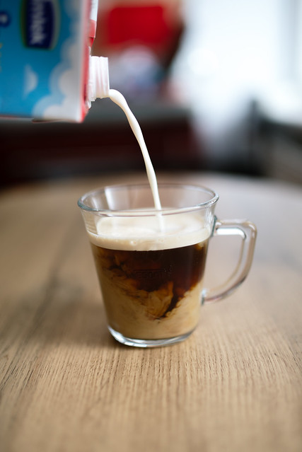 Closeup of milk into glass cup of coffee. Pouring milk concept.