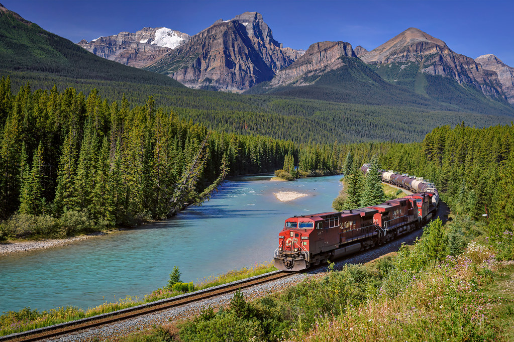 A Canadian Pacific Railway train rounds the bend at Morant's Curve along the Bow River, Bow Valley Parkway in Banff National Park, Alberta, Canada