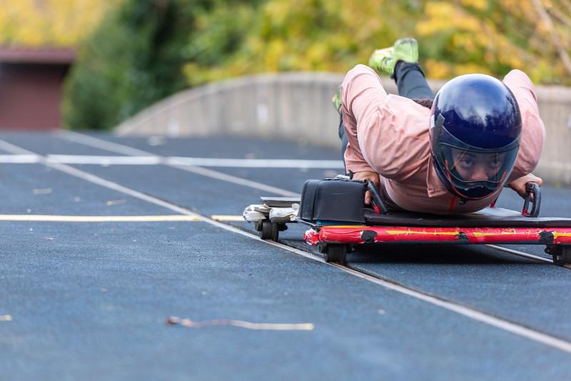 Boy in a black crash helmet lying on a red bob sleigh board on the track