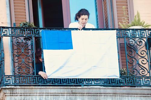Herritar bat Donostiako bandera jartzen bere balkoian