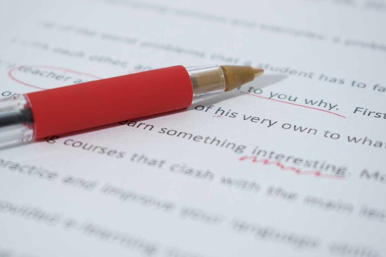 Page of academic writing with some words circled and a red pen resting on top.