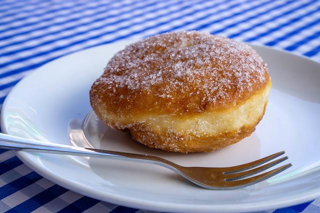Berliner Pfannkuchen mit Vanillecreme und Zucker auf einem Teller mit einer Gabel Nahaufnahme