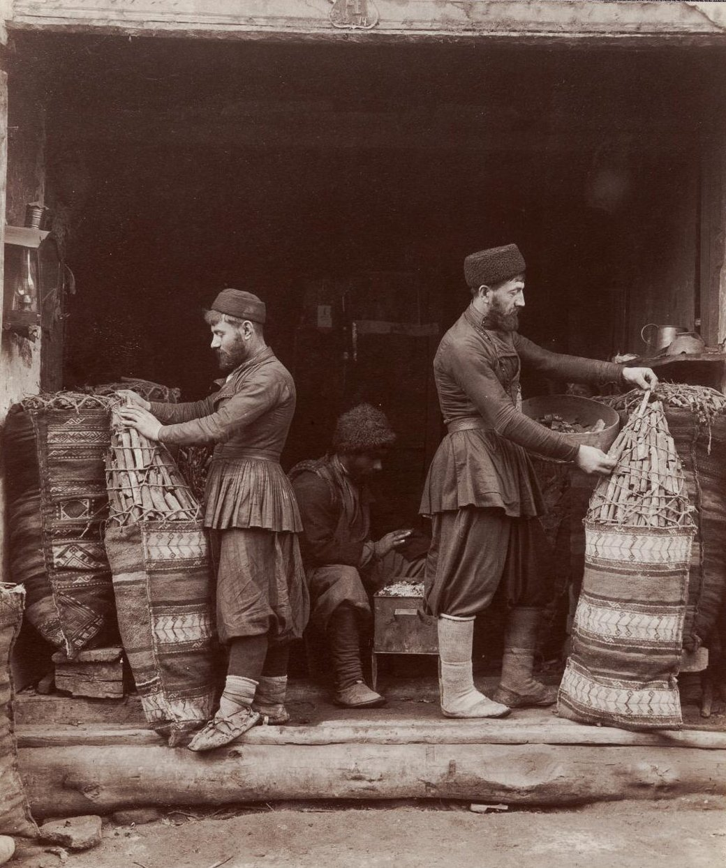 Угольщики, укладывающие угли и муша, греющий руки над мангалом