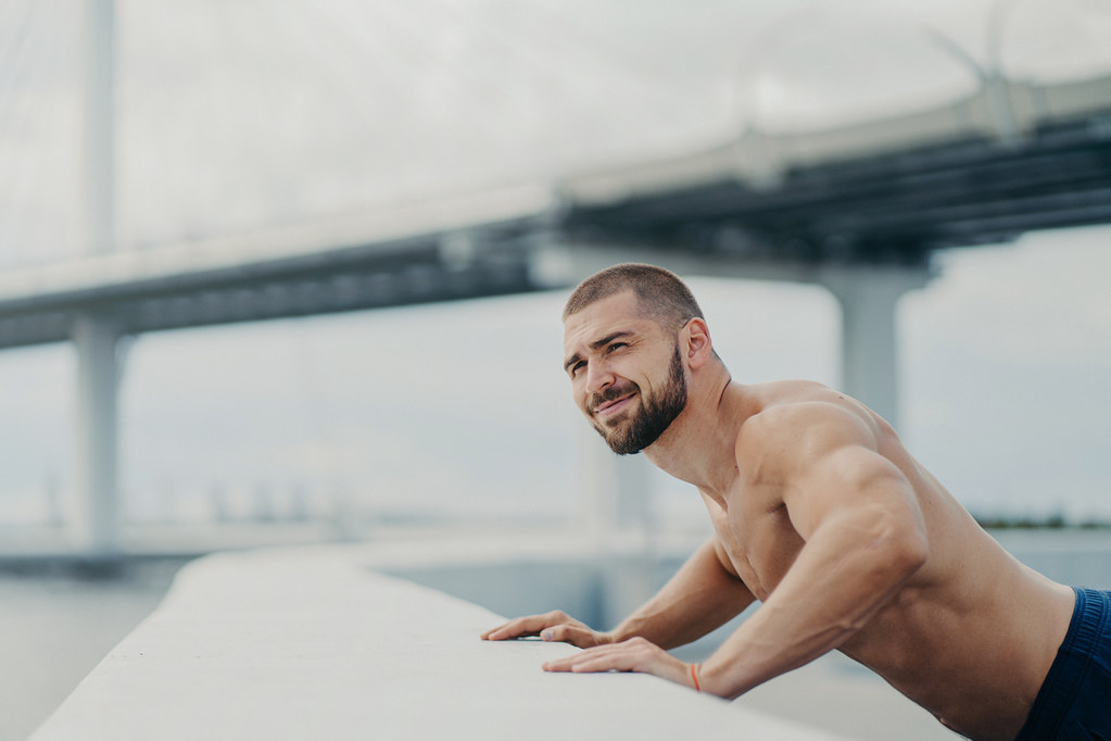 Strong bearded Caucasian man trains muscles and does push ups exercises, tries to reach fitness goals, demonstrates his physical strength, has naked torso, poses outdoor over bridge background.
