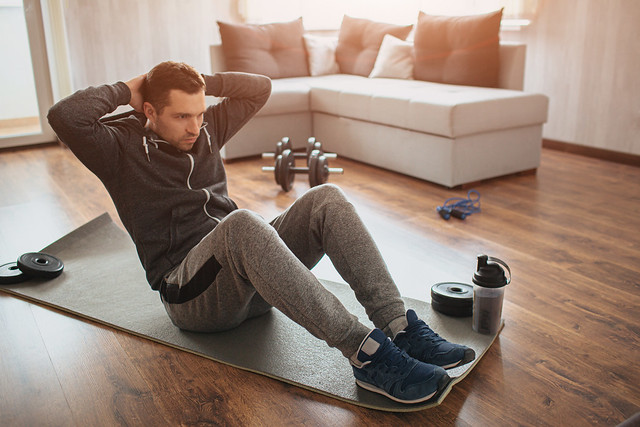 Young ordinary man go in for sport at home. Hardworking freshman sit on mat and do abs excercise. Not easy to start workout alone in apatment. Beginner in action. Sport equipment on floor.