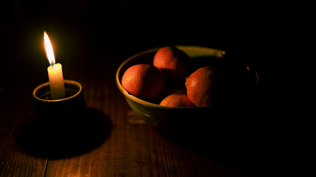 CANDLE AND A BOWL FULL OF ORANGES