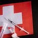 Vaccine vial. Medical syringe with needle for protection flu virus and coronavirus with flag of Switzerland
