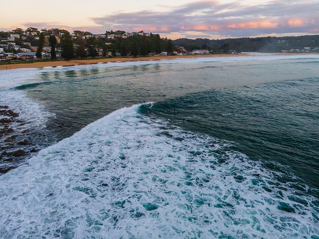 Early morning aerial at the beach with surfers