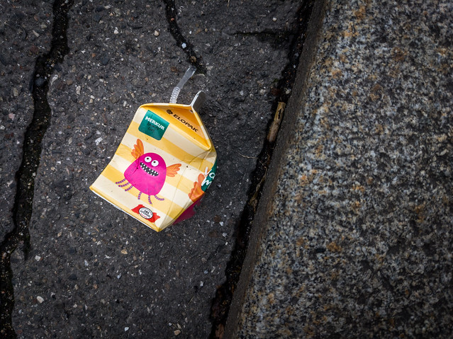 Cardboard juice pack and a plastic straw thrown on the ground