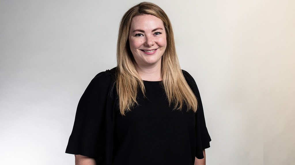 MSc in Sustainability and Management student Gillian Jacques wearing a short sleeve black blouse stands in front of a light grey studio backdrop smiling at the camera.