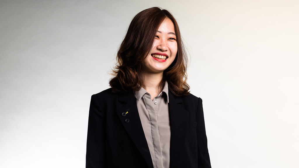 Wearing a black blazer and a light grey shirt, MSc in Human Resource Management and Consulting student Ge Bai stands in front of a light grey studio backdrop smiling at the camera.