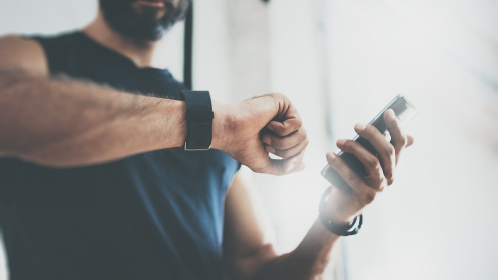 Man looking at smart watch mid exercise.