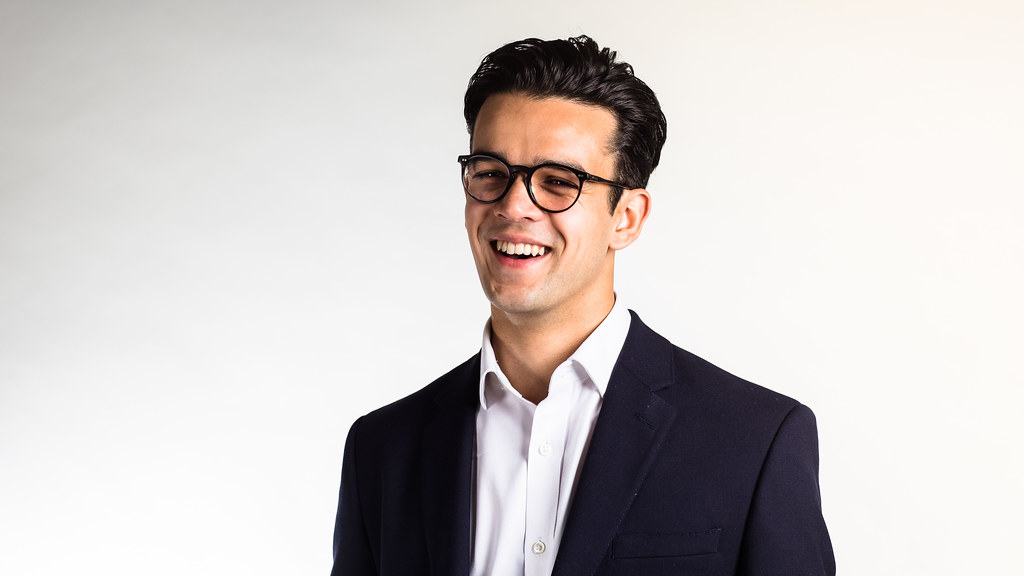 Wearing a black blazer and a white shirt, MSc in Innovation and Technology Management student Max Tomlinson stands in front of a light grey studio backdrop smiling at the camera.