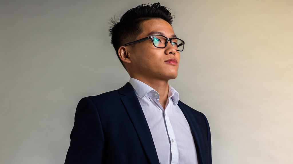 Wearing a dark blue blazer and a white shirt, MSc in Operations, Logistics and Supply Chain Management student Songbin Lyu stands in front of a light grey studio backdrop staring up and away from the camera.