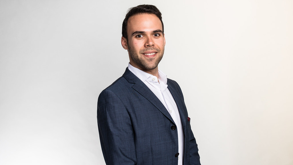 Wearing a dark blue blazer and a white shirt, MSc in Entrepreneurship and Management student Nicolas Louca stands in front of a light grey studio backdrop smiling at the camera.