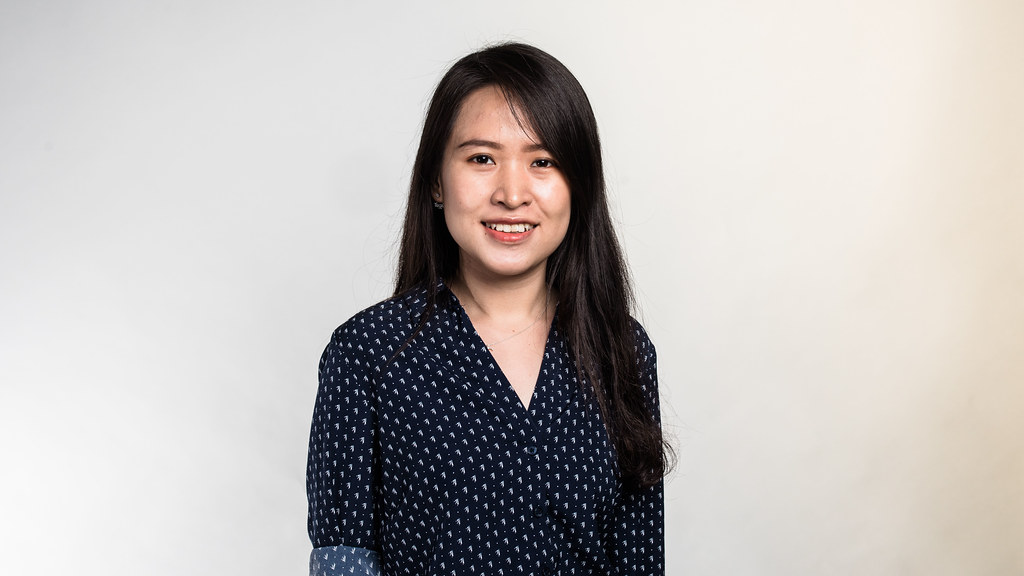 MSc in Accounting and Finance student Huyen Nguyen wearing a blue and white patterned blouse stands in front of a light grey studio backdrop smiling at the camera.