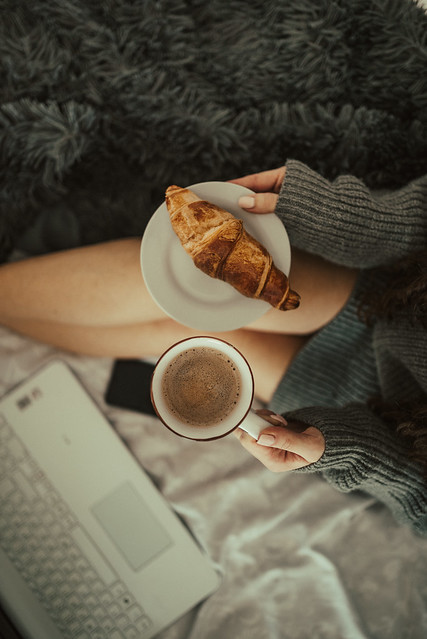 Woman holding croissant and cup of coffee from above.