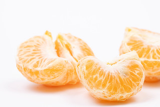 Tangerine slices above white background | by wuestenigel