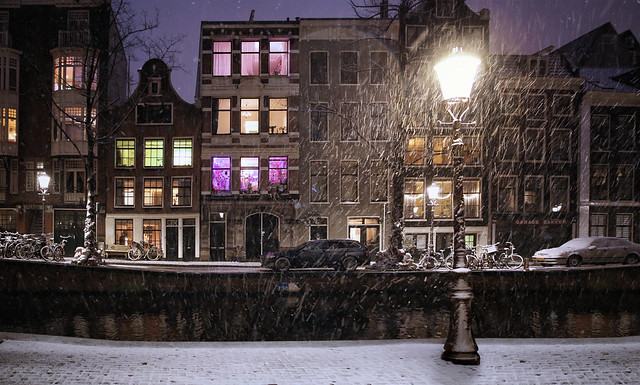Snow falls silently in the early evening on the Amsterdam canals
