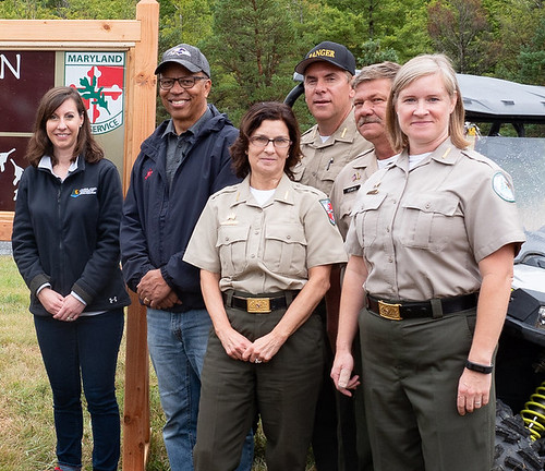 Photo of officials standing at Wolf Den Run State Park entrance sign