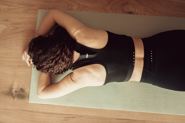 A tired woman in sportswear lying on the floor. Top view.