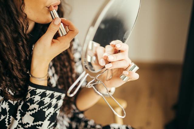 Attractive woman applying her makeup. Applying lipstick closeup.