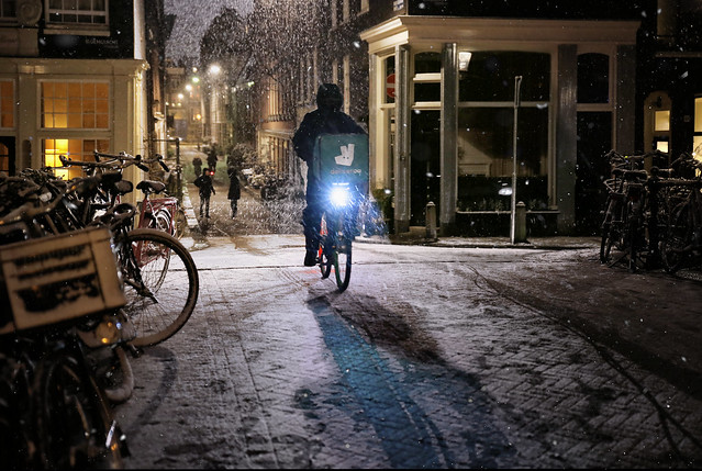 Deliveroo rider in snowfall at the Bloemgracht