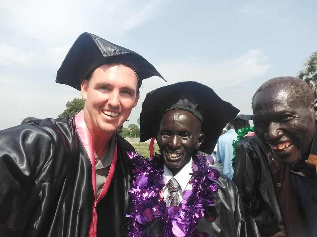 Three men stand smiling together in graduation regalia.