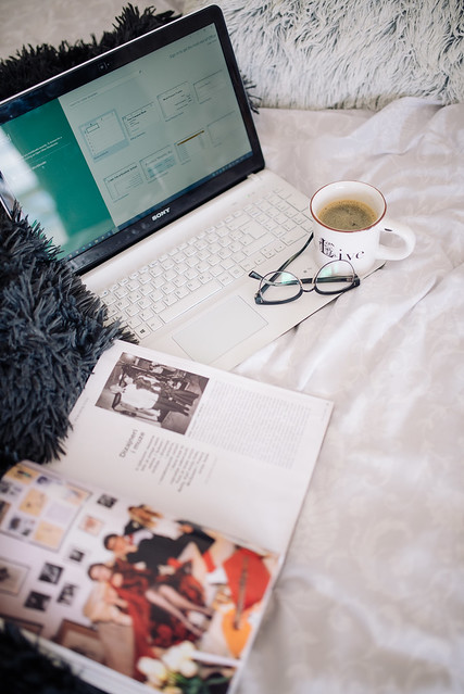 Magazine, laptop, cup of coffee and glasses on bed.