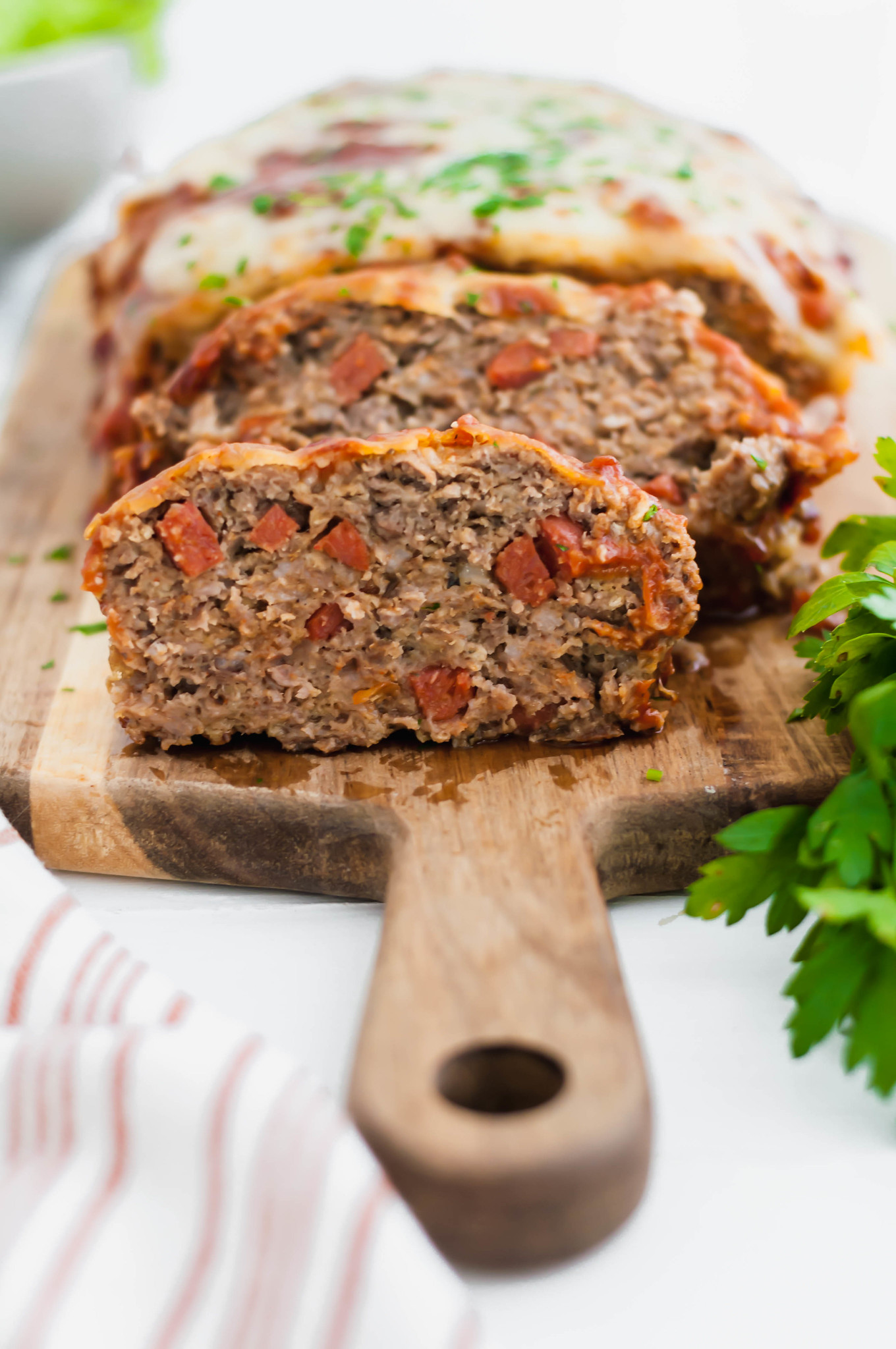 Two dinnertime favorite collide with this Pizza Meatloaf. Pizza ingredients throughout the meatloaf and on top puts that pizza flavor over the top.
