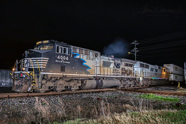 """NS 124 heads north crossing the CSX interlocking in Valdosta with """"horse-mane""""units 4004 and 1800 doing the honors."""