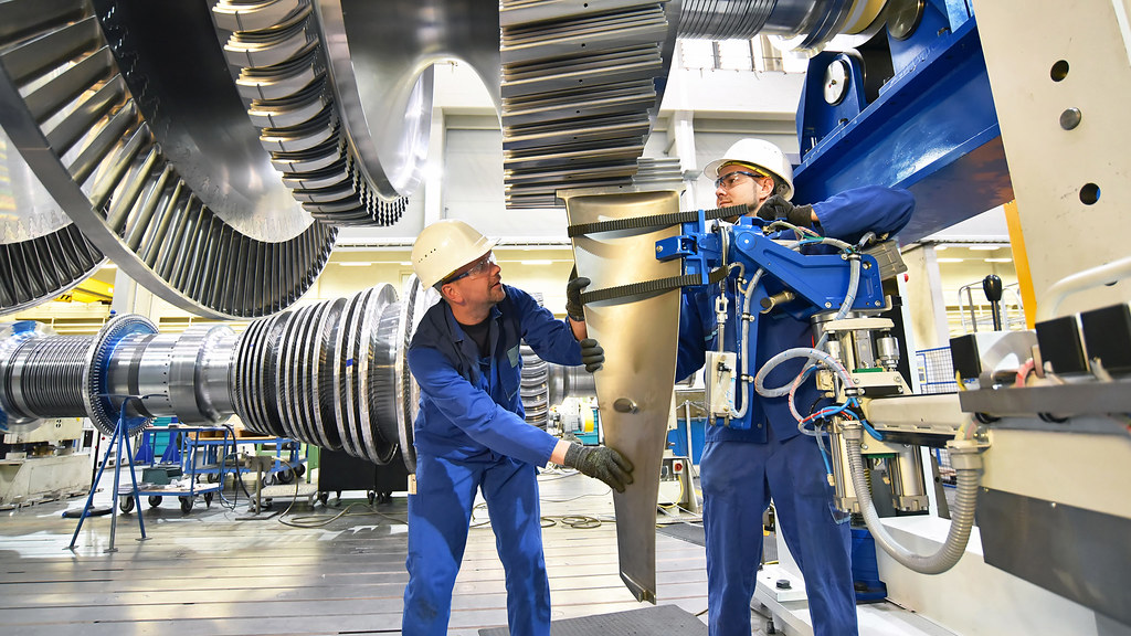 Two workers assemble a huge power turbine above their heads.