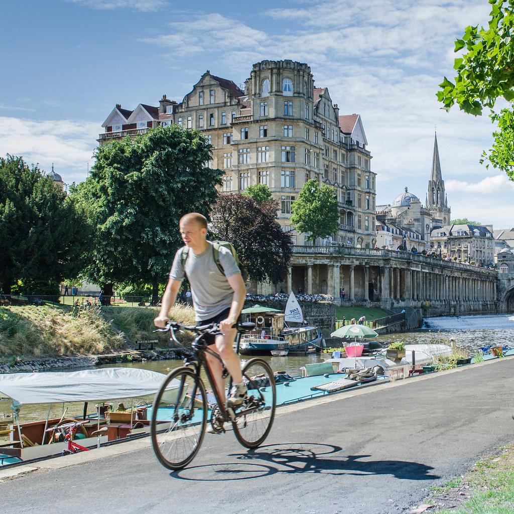 A cyclist beside the River Avon.