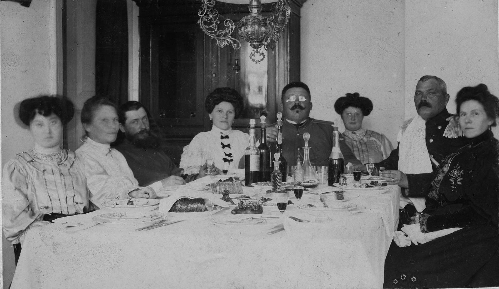 Брандмайор А.Ф. Домишкевич, сидящий в форменной одежде за накрытым праздничным столом