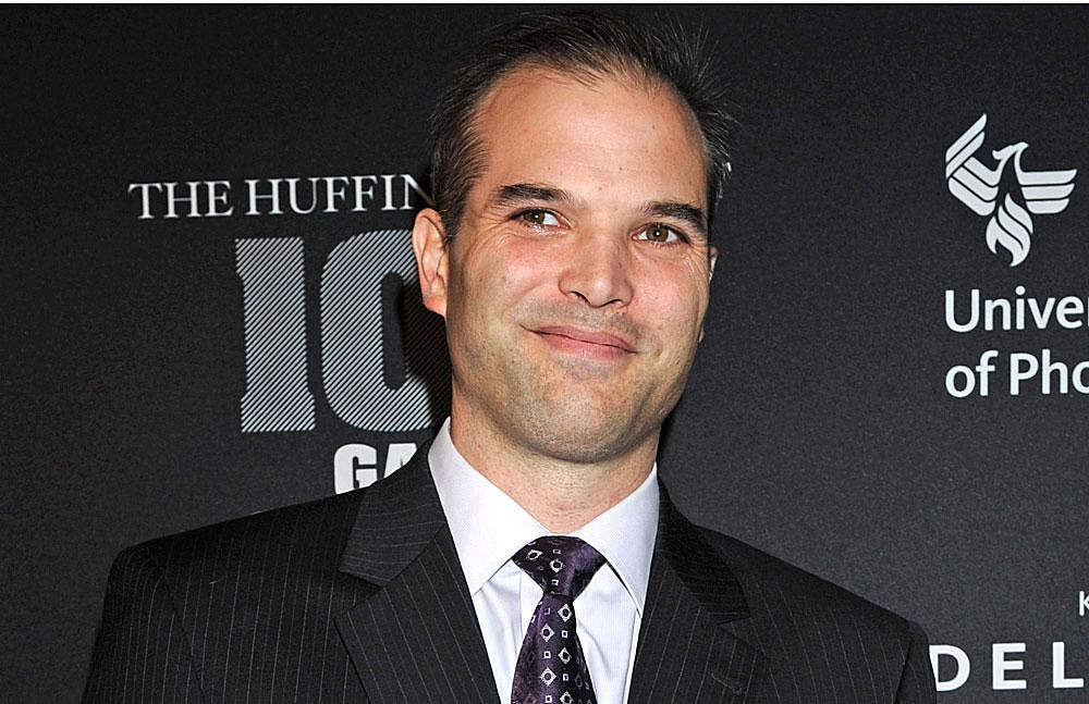 A photo of Matt Taibbi at a Huffington Post event with a promotional banner wall behind him. He is wearing a charcoal pinstripe suite and an ugly purple tie