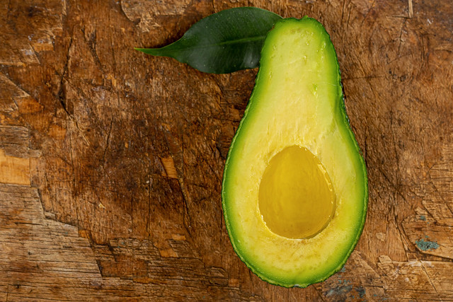 Top view, half a ripe avocado with oil and green leaf on an old wooden background